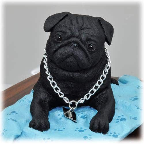 Black pug figurine on blanket, detail